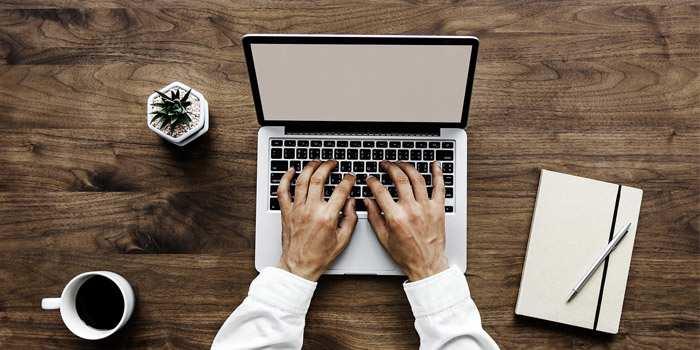 Persona che scrive al pc su scrivania